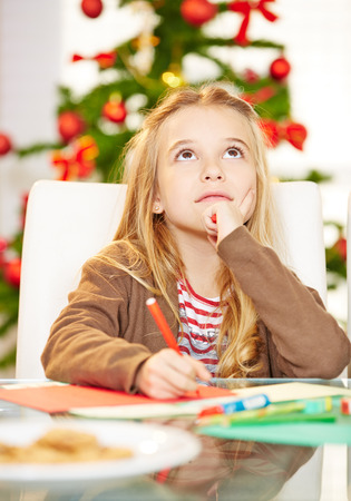 write a letter: Pensive child writing wishlist to Santa Claus for christmas Stock Photo