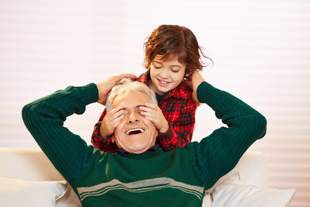 guess: Boy holding the eyes closed of his happy grandfather Stock Photo