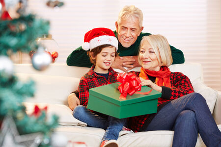 Boy opening gift at christmas with his grandparents photo