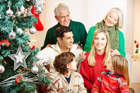 Smiling woman and her family celebrating christmas at home with tree photo