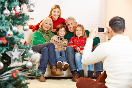 Father taking family picture at christmas with his smartphone photo