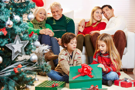 Happy children opening gifts at christmas while parents and grandparents are watching photo