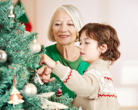 decorating christmas tree: Grandmother and grandchild decorating christmas tree at home Stock Photo