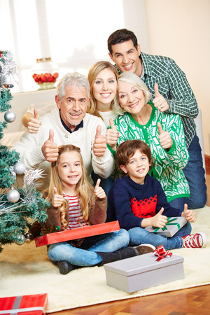 Happy family at christmas with gifts holding thumbs up photo