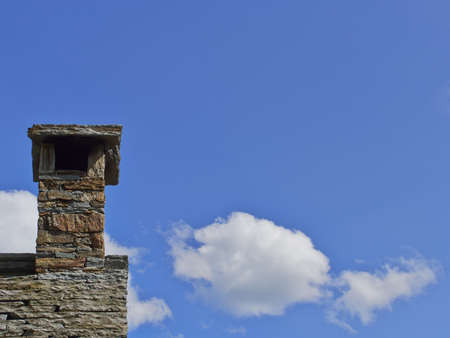 slate roof: Chimney on an old slate roof with blue sky and some clouds