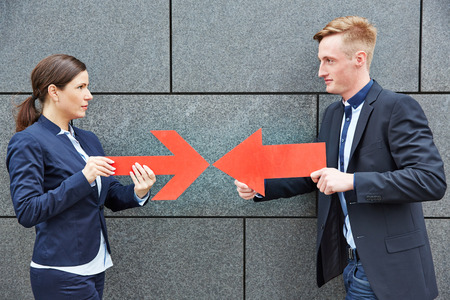 opponents: Two opponents holding two big red arrows against each other Stock Photo