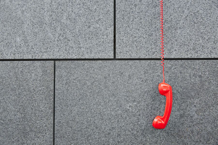 cry for help: Red emercency call phone hanging down on a wall