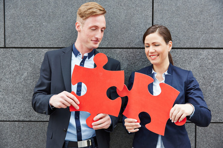 Two business people solving big red jigsaw puzzle pieces photo