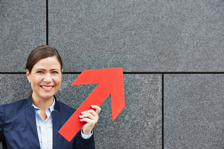 Smiling business woman holding big red arrow up