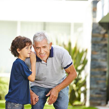 Kleinzoon fluisteren een geheim in het oor van zijn grootvader buitenshuis