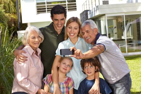 Autofoto de familia en tres generaciones con niños en verano en frente de una casa