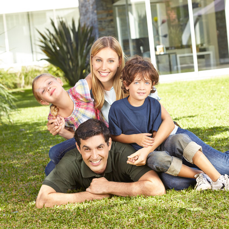 Happy family with daughter and son laying in a garden in front of house photo