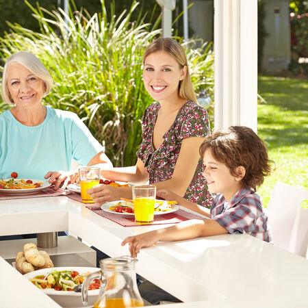 sunroom: Child eating lunch salad with mother and grandmother in summer Stock Photo