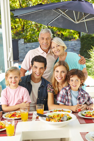 Happy vegetarian family eating healthy with salad at lunch photo
