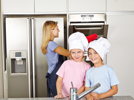 family kitchen: Two happy children in kitchen with cook hats with their mother Stock Photo
