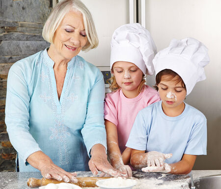 Two children cooking together with grandmother for christmas in a kitchen photo