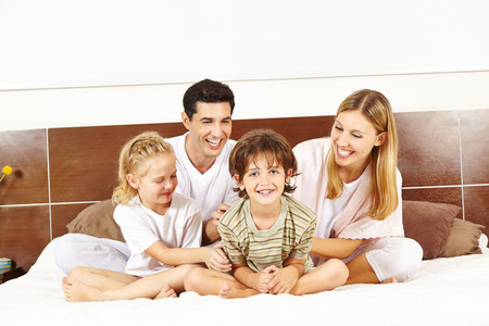 Happy family with two children sitting in bed in the morning photo