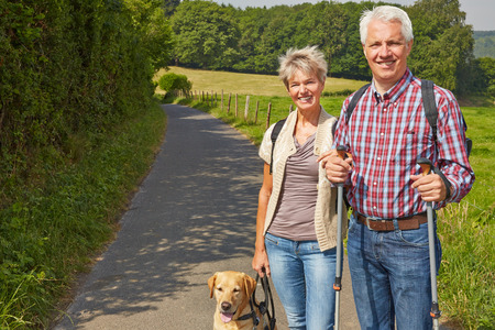 Happy senior couple hiking with their dog in nature in summer photo