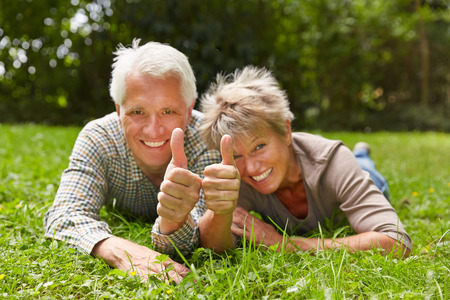 Two happy senior people laying in a meadow holding their thumbs up photo