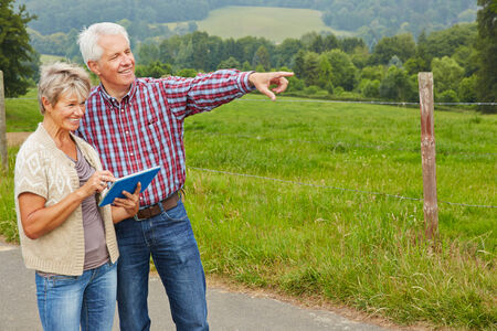 Happy senior couple looking for directions with tablet computer while hiking photo