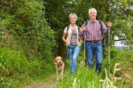 persona de la tercera edad: Feliz pareja senior haciendo Nordic Walking con el perro en un bosque