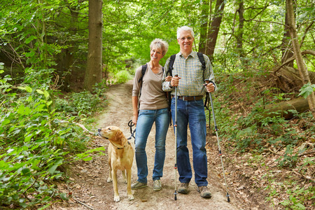 Smiling senior couple on a hike walking with a dog in a forest photo