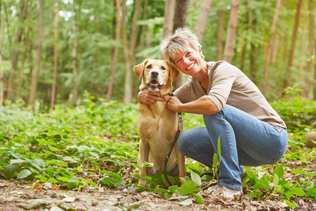Labrador Retriever sitting with elderly woman in a forest