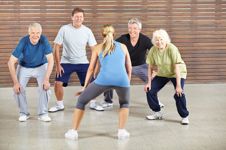 Personas mayores bailando a la música en el gimnasio con instructor de baile Foto de archivo