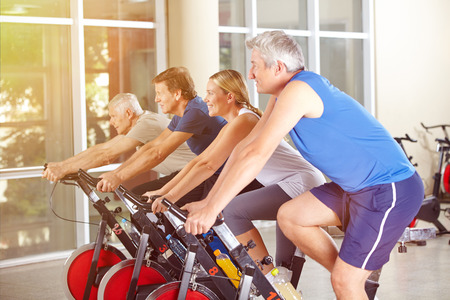 Happy group in gym exercising on spinning bikes in summer photo