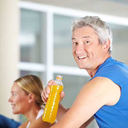isotonic: Elderly man drinking isotonic sports drink in a gym