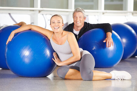Two happy senior people sitting in gym with exercise ball photo