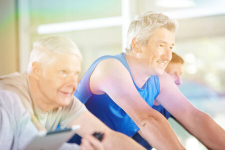 Happy senior people exercising on spinning bikes in gym in summer photo