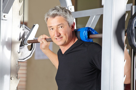 muscle formation: Man lifting barbell in fitness center as part of his gym training Stock Photo
