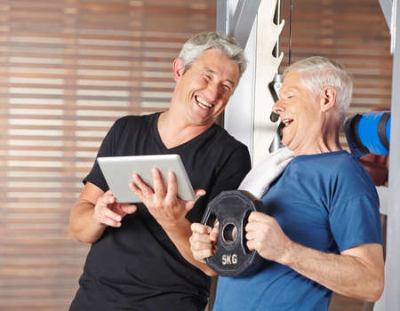 muscle formation: Senior men exercising in gym and laughing with tablet PC Stock Photo