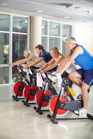 Happy senior group exercising in spinning class in a gym photo