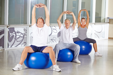 muscle formation: Group of senior people stretching in gym on exercise balls