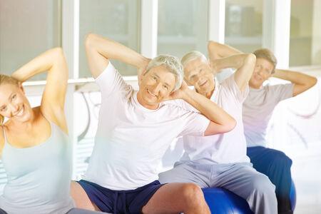 pilates ball: Happy senior group doing back training in gym on exercise balls