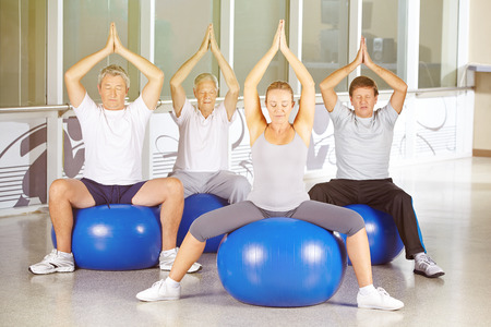 Senior group exercising in yoga class in gym photo