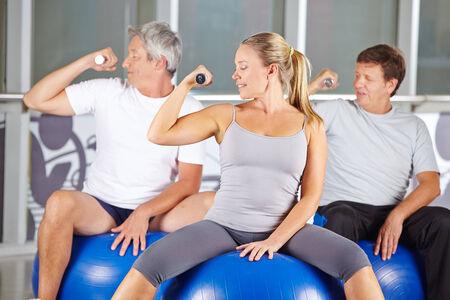 senior group: Senior group doing dumbbell training in gym while sitting on exercise balls