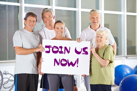 advertise with us: Group of senior poeple holding a Join us now sign in a gym