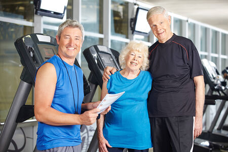 senior citizen: Happy senior couple with personal trainer in fitness center at treadmill