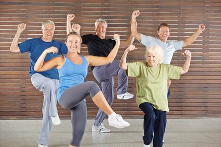 Grupo mayor feliz haciendo una clase Bokwa en el gimnasio