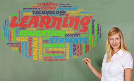 traineeship: Smiling woman drawing learning and education tag cloud on a chalkboard