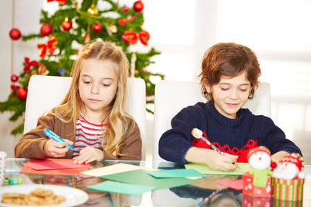 Two siblings drawing cards at christmas with handicrafts photo