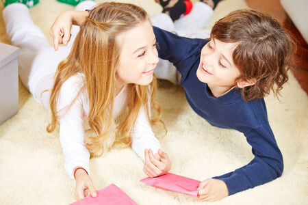 wishlist: Two happy siblings with greetings cards embracing each other