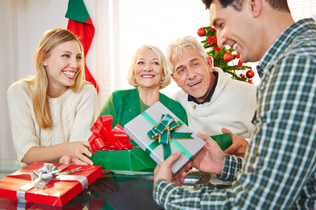 Happy couple celebrating christmas eve with gifts and seniors photo