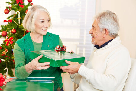 Two happy senior citizens celebrating christmas with gifts photo