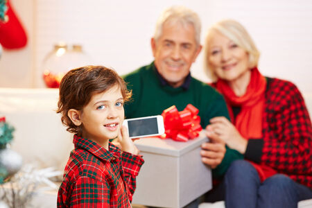 Child taking smartphone picture of grandparents at christmas photo