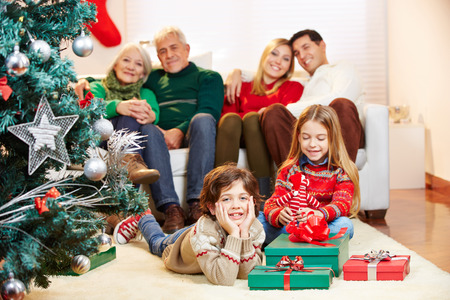 Happy family sitting with gifts at christmas tree at home photo