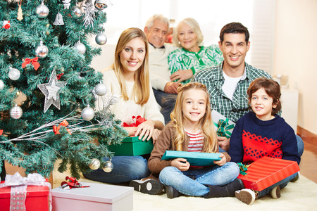 Family celebrating christmas with three generations under tree with gifts photo